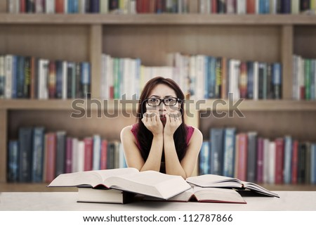 Portrait of frightened female college student with textbooks biting her nails. shot in the library