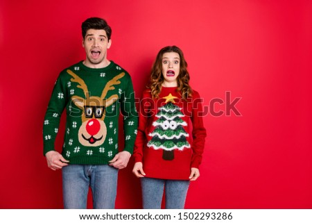 Portrait of frustrated frightened two youth people with brunette wavy hair dislike christmas tree pattern decor jumper shout omg wear denim jeans isolated over red color background