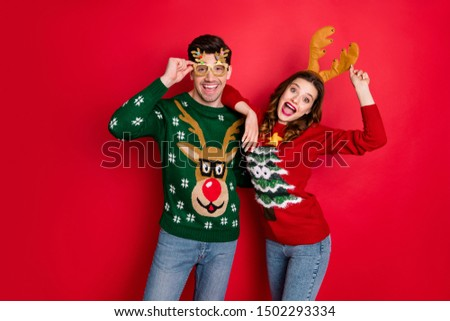 Portrait of funky crazy two people  wife husband in brown antlers costume lean shoulder wear denim seasonal clothes christmas tree design pullover jumper spectacles isolated over red color background #1502293334