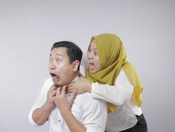 Portrait of funny Asian muslim couple having conflict, wife and husband fight, violence in family, husband afraid to his wife concept