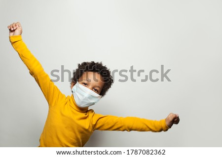 Portrait of funny black child boy in medical protective face mask having fun