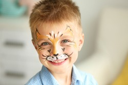 Portrait of funny boy with face painting on blurred background