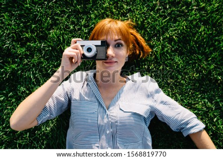 Portrait of funny caucasian woman lying on green grass making picture on vintage camera during free time,female photographing amateur satisfied with old retro equipment taking pictures outdoors