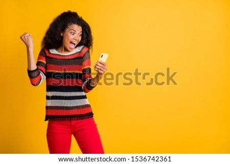 Portrait of funny crazy girl get feedback read feed news on smartphone feel impressed expression scream wow omg wear striped shirt red pants copyspace isolated yellow color background