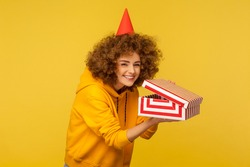 Portrait of funny curly-haired woman with party cone hat looking at camera with cunning smile and holding unpacked gift box, smirking as if planning devious prank. indoor studio shot, isolated