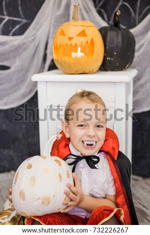 Portrait of funny cute little boy in costume of vampire holding holiday pumpkin in hands. Halloween decor in black and white colors. Vertical color photo.