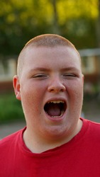 Portrait of funny fat teenager in red shirt with buzz cut. Boy opened mouth widely