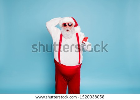 Portrait of funny funky fat modern santa claus in sunglass use his cell phone got christmas time blogs notification scream wow omg wear red suspenders overalls isolated over blue color background