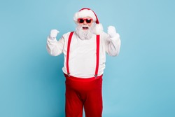 Portrait of funny funky fat santa claus with big belly raise fists scream yeah have luck celebrate newyear x-mas party wear suspenders modern red spectacles isolated over blue color background