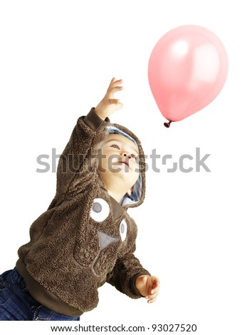 portrait of funny kid trying to hold a pink balloon over white background