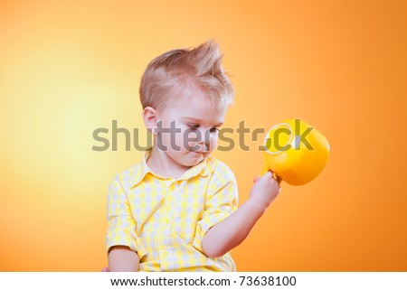 Portrait of funny little boy showing big yellow empty cup