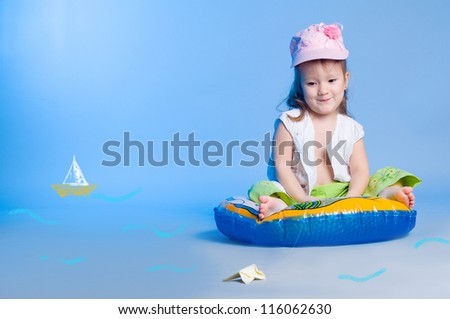 Portrait of funny little girl fishing in a studio and looking at a drawn fish