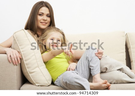 Portrait of funny lovely little girl with mother sitting on sofa