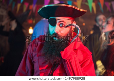 Portrait of funny man in a pirate costume playing with his hand hook at halloween celebration. Cheerful pirate.