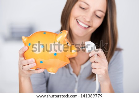 Portrait of funny mid adult woman holding electric plug and piggy bank