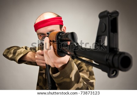 Portrait of funny soldier aiming with machine gun