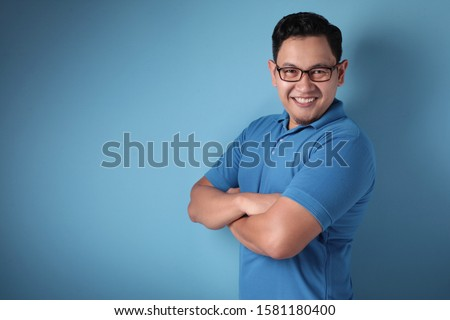 Portrait of funny young attractive cute Asian man smiling happily, with arms crossed, against blue background