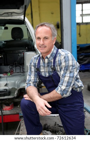 Portrait of garage owner standing by vehicle