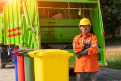 Portrait of garbage collector with truck loading waste and trash bin.