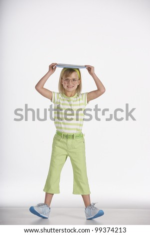 Portrait of girl balancing book in head