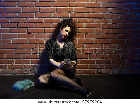 portrait of girl dressed like hooker posing near brick wall #57979204