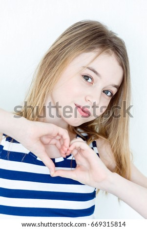 Portrait of girl eleven years old with big green eyes shows heart #669315814