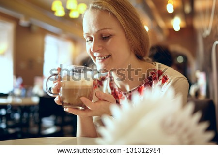 Portrait of girl enjoying coffee latte in cafe. Beautiful vintage interior in blur with natural sunlight.