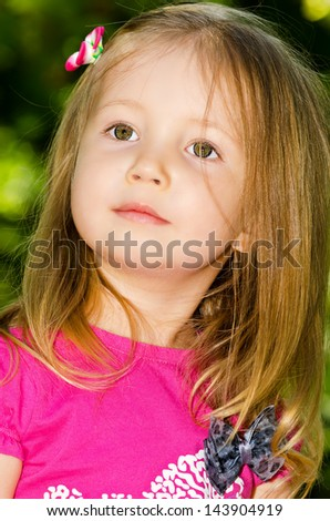 Portrait of girl in a red sport shirt on a background green trees.