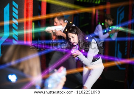 Portrait of girl in colored beams of laser guns during laser tag game on dark arena