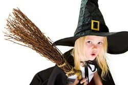 Portrait of girl in halloween costume and broom with frightening expression