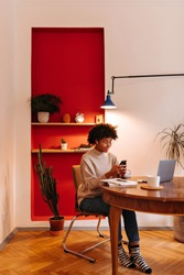 Portrait of girl in jeans, sweater and striped socks, looking at phone and sitting in home office