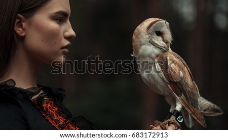 Portrait of girl in red and black dress with owl in hand. Close-up.