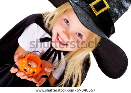 Portrait of girl in witch costume and small pumpkin candle in hands
