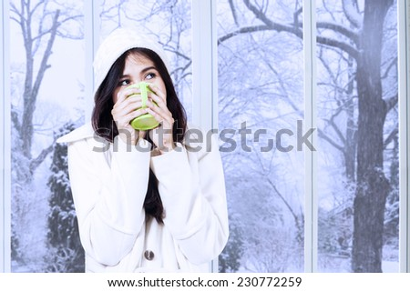 Portrait of girl relaxed at home in winter holiday and enjoy a warm drink while wearing a winter coat