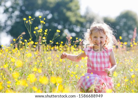 Portrait of girl running through wildflower meadow smiling at camera