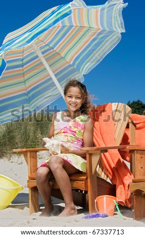 Portrait of girl sitting in chair with umbrella at beach