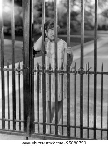 Portrait of girl through bars of fence - stock photo