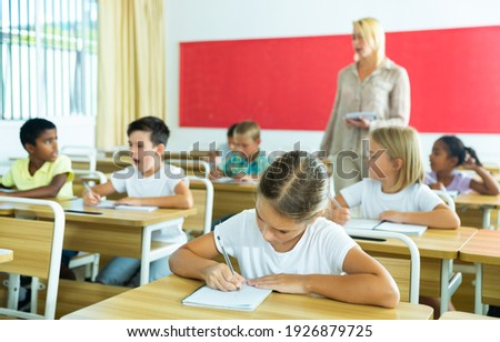 Portrait of girl who is posing at the desk in the classroom elementary school Photo stock ©