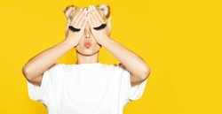 Portrait of girl with blond hair sending air kiss with fake eyelash on hands on yellow background. Concept of emotions.