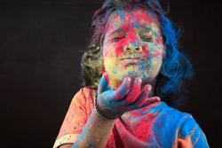 Portrait of girl with face smeared with colors blows colos in a dark background. Concept for Indian festival Holi.