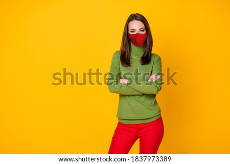 Portrait of girl with folded arms wearing red fabric face mask isolated over bright yellow color background Stockfoto ©