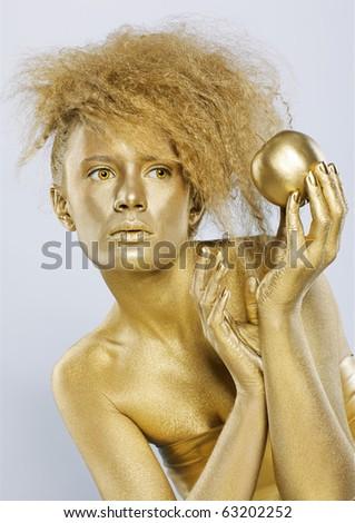 portrait of girl with golden bodyart posing with golden apple in her hands on gray