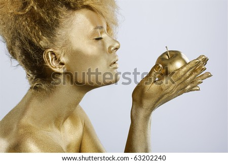 portrait of girl with golden bodyart smelling golden apple in her hands on gray