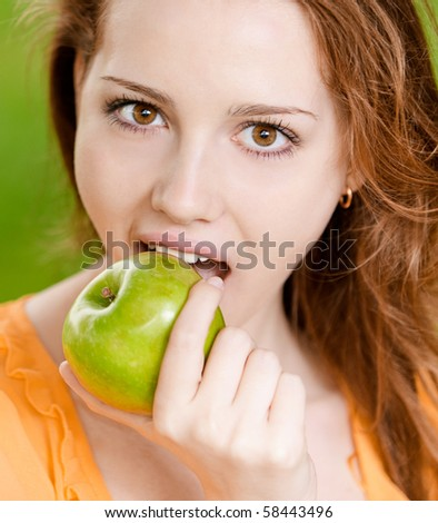 Portrait of girl with green apple against green grass.