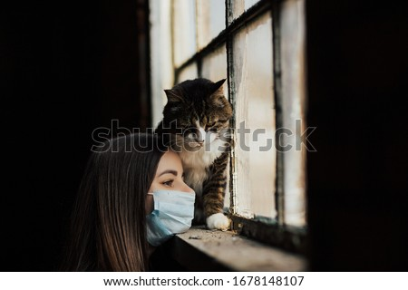 Portrait of girl with her lovely sad cat near old window in village house during of coronavirus quarantine. Sad cat by the window. Coronavirus time.