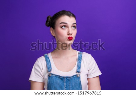 Portrait of girl with two hair-buns, tight red lips, wearing denim overalls and pink t-shirt isolated looks up making lips bow on purple background Stock photo ©