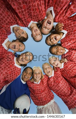 Portrait of girls\' soccer team forming a huddle against clear blue sky
