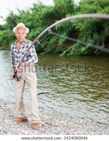 Portrait of glad aged fisherman with angling gear stretched by catch fish