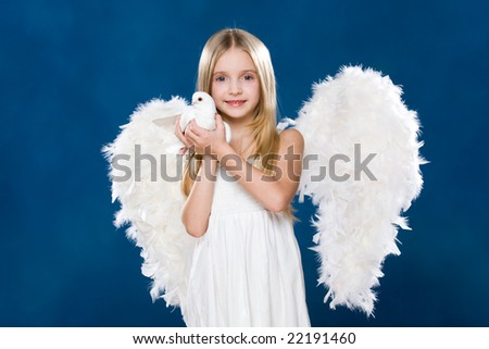 Portrait of glad angel holding white dove in hands and looking at camera
