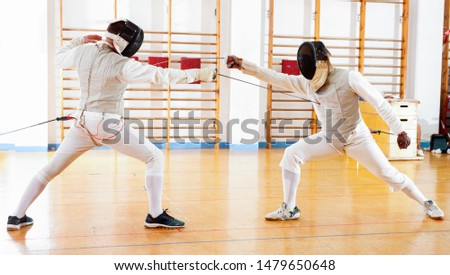 Portrait of glad cheerful positive athletes at fencing workout, practicing attack movements in duel  #1479650648